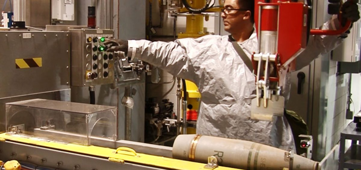A Pueblo Chemical Agent-Destruction Pilot Plant ordnance technician places a 155mm munition on a conveyor as part of the process of eliminating the agent-filled projectile.