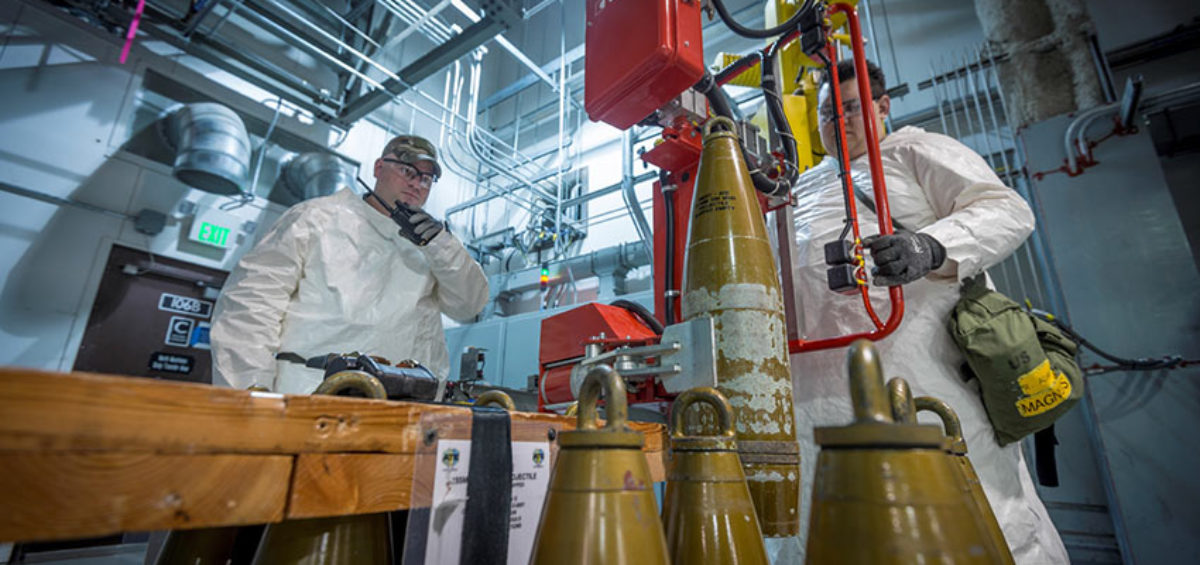 An ordnance technician uses a lift assist to place a simulated munition onto a conveyor as a part of systemization activities. The systemization phase is nearing completion at the Pueblo Chemical Agent-Destruction Pilot Plant.