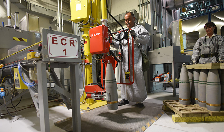 An ordnance technician at the Pueblo Chemical Agent-Destruction Pilot Plant handles 155mm projectiles containing mustard agent for processing.
