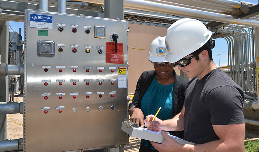 Electrical Engineer Interns Ciera Gooden and Kody Kovacich examine a power panel that distributes energy to different areas of a facility.