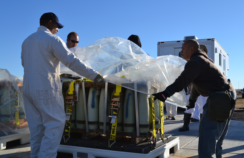 U.S. Army Pueblo Chemical Depot toxic materials handlers shroud an overpacked pallet with mock munitions as part of a training exercise.