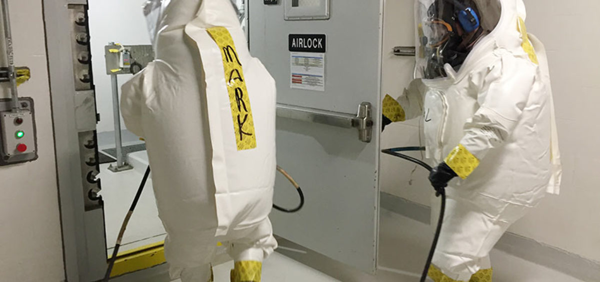 An entry support area tender and ordnance technician perform a practice Demilitarization Protective Ensemble entry in the Agent Processing Building. The Chemical Agent Safety Team was established at the Pueblo plant to make toxic area entries safer and more efficient.