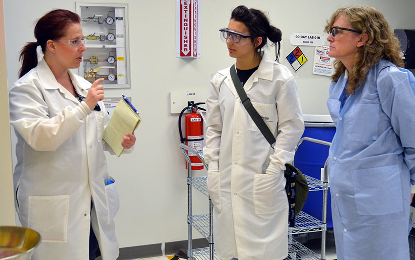 Mechelle Cass-Burrell, gas chromatography/flame photometric detector/mass selective detector operator, explains laboratory processes to intern Alexa Snyder and faculty supervisor Dr. Helen Caprioglio.