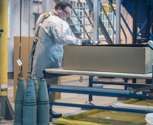 A munitions handler marks a box containing mustard agent-filled projectiles prior to destruction in the Explosive Destruction Technology facility at the Blue Grass Chemical Agent-Destruction Pilot Plant. Destruction of 50% of the mustard munitions was achieved Sept. 1.