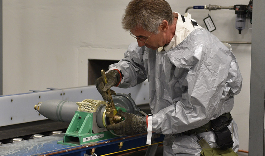 A Pueblo Chemical Agent-Destruction Pilot Plant ordnance technician and baseline reconfiguration team member remove the rear assembly from a 4.2-inch mortar round. The plant has completed this campaign and the rounds will be destroyed in Static Detonation Chamber units.