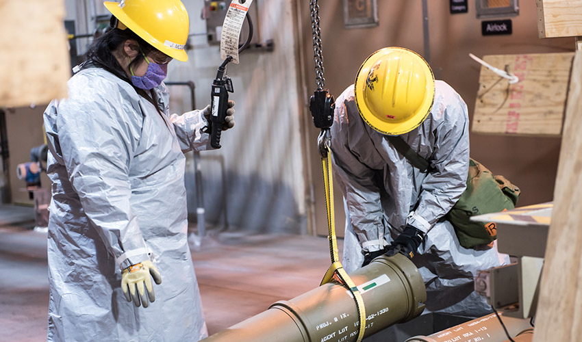 Two operators work together to place one of the last overpacked 8-inch projectiles containing nerve agent into a tray to begin the destruction process at the Blue Grass Chemical Agent-Destruction Pilot Plant May 9. The last GB 8-inch projectile was destroyed May 11, marking the complete destruction of an entire type of chemical weapon.