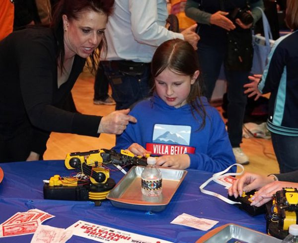 Mechelle Cass-Burrell, a laboratory operator at the Pueblo Chemical Agent-Destruction Pilot Plant, uses a toy robot to help a student at the Pueblo School District 60 STEM Fair in January 2020 understand the technology destroying chemical weapons.