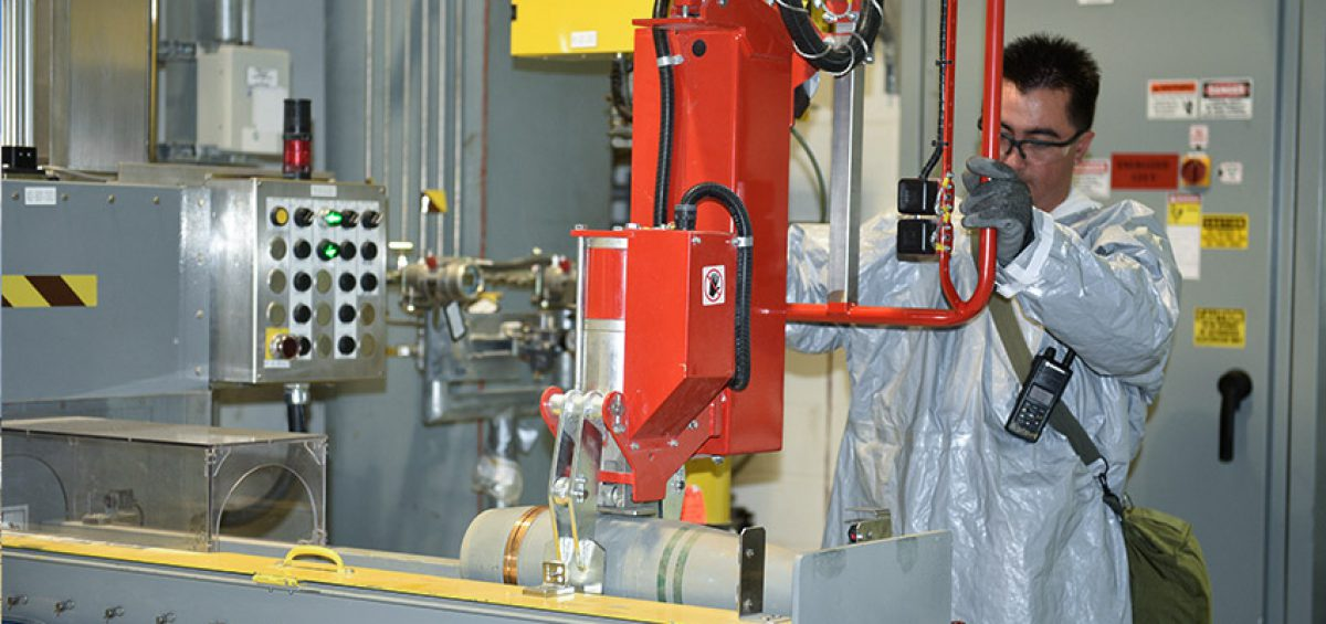 An ordnance technician uses a lift-assist device at the Pueblo Chemical Agent-Destruction Pilot Plant to place a 155mm projectile containing mustard agent onto a conveyor belt in the Enhanced Reconfiguration Building.