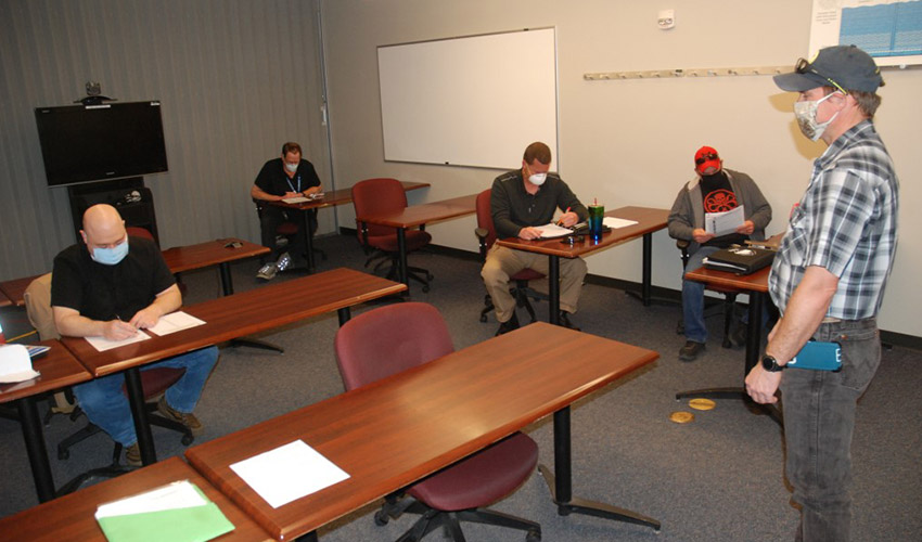 Image of in-person training class with masked personnel.