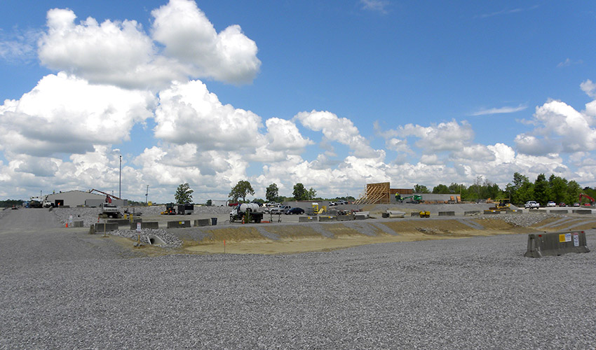 The Static Detonation Chamber 2000 site stands just north of the Blue Grass Chemical Agent-Destruction Pilot Plant. Placement of the Personnel Support Building (structure at far left) and the Earth-Covered Magazine (structure at far right) is quickly progressing.