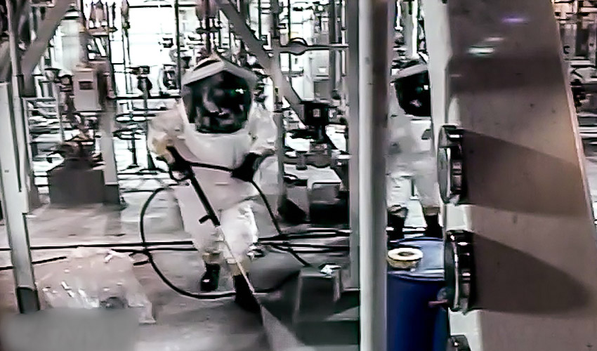Toxic Area entrants decontaminate the Agent Neutralization System room at the Blue Grass Chemical Agent-Destruction Pilot Plant with a caustic solution after the conclusion of the GB 8-inch projectile campaign. (Still image from closed-circuit television.)