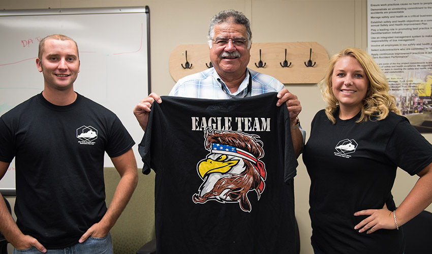 Three members of the Environmental Action Group Led by Employees, or EAGLE, team pose with team shirts at the Blue Grass Chemical Agent-Destruction Pilot Plant. The EAGLE team was created when employees saw an opportunity to focus on potential environmental issues.