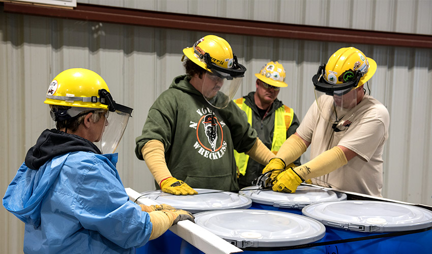 Waste operators band drums on a pallet at the Blue Grass Chemical Agent-Destruction Pilot Plant Container Storage Facility during a waste shipment demonstration. During operations, contaminated secondary wastes may be shipped off site to a permitted and licensed waste treatment, storage and disposal facility.