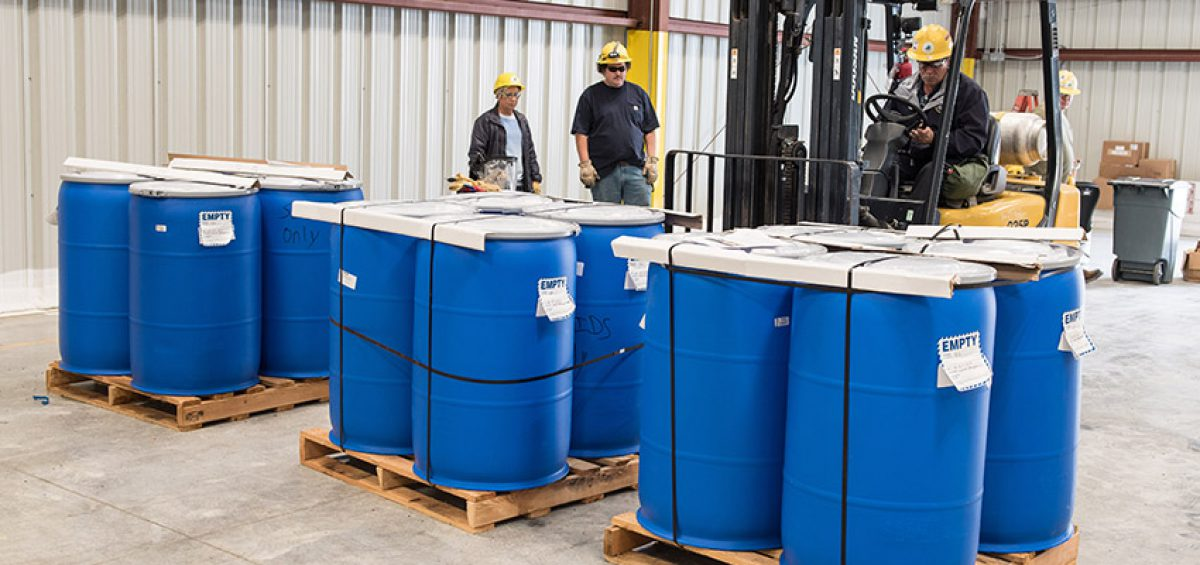 A waste operator practices moving waste drums on pallets at the Blue Grass Chemical Agent-Destruction Pilot Plant Container Storage Facility. The plant's hazardous waste is regulated by a standard hazardous waste permit through the Kentucky Department for Environmental Protection.