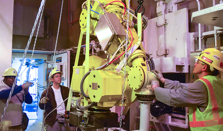 Technicians remove a robot from the Energetics Batch Hydrolyzer room at the Blue Grass Chemical Agent-Destruction Pilot Plant. Static Detonation Chamber systems will destroy drained rocket warheads, including the energetics, which reduces risk to the workers.