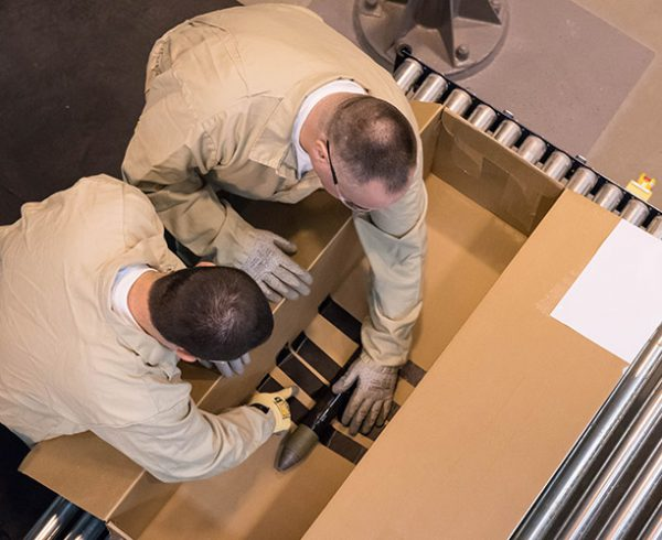 Munitions handlers secure a conventional munition in a box prior to it being processed in the Static Detonation Chamber at the Blue Grass Chemical Agent-Destruction Pilot Plant. This test shot will commission the chamber for use in operations.