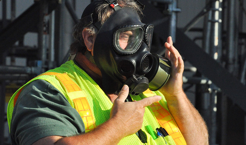 A worker checks a mask after donning it for an annual emergency preparedness exercise at the Blue Grass Chemical Agent-Destruction Pilot Plant Sept. 18. Plant workers participated in this multi-county exercise, along with city, county, state and federal organizations and personnel.