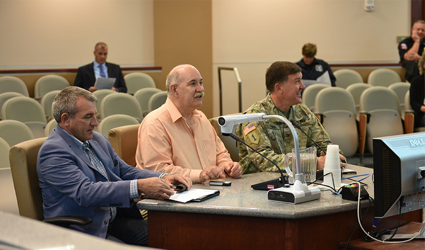 From left, Ken Harrawood, project manager, Bechtel Pueblo Team, Walton Levi, site project manager, Pueblo Chemical Agent-Destruction Pilot Plant, and Col. Michael Cobb, military commander, Pueblo Chemical Depot, give the Pueblo City Council a briefing Oct. 15, 2019, on the status of the destruction of the stockpile of mustard agent-filled munitions.