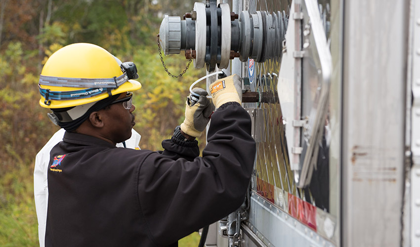 A technician attaches an air-sampling tube to a tractor trailer as part of a waste shipment demonstration prior to Blue Grass Chemical Agent-Destruction Pilot Plant main plant operations.