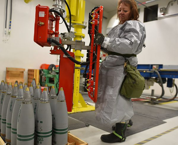 A worker at the Pueblo Chemical Agent-Destruction Pilot Plant places 105mm projectiles that have been unboxed and reconfigured for processing on a pallet using a motorized lift assist.