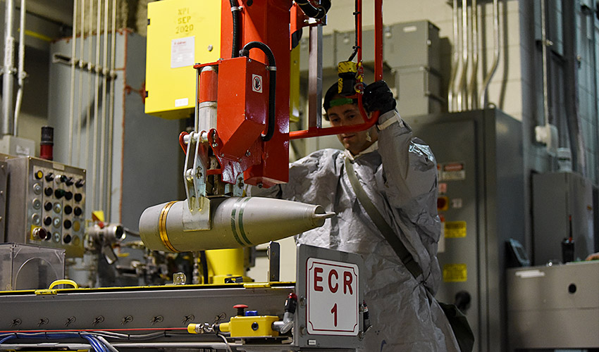A Pueblo Chemical Agent-Destruction Pilot Plant ordnance technician uses a lift-assist device to transfer 155mm projectiles from a pallet to the automated processing line for disassembly and draining. In July 2019, the plant exceeded the halfway point for the 155mm destruction campaign.