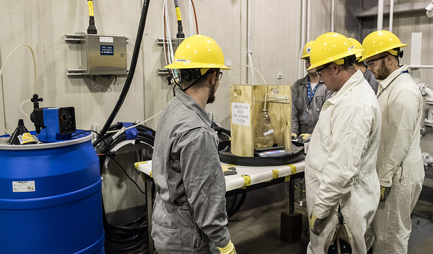 Technicians weigh a sample of chlorobenzene to calibrate a pump in preparation for surrogate testing at the Blue Grass Chemical Agent-Destruction Pilot Plant. The plant is using surrogate chemicals to be able to prove destruction of chemical agent.