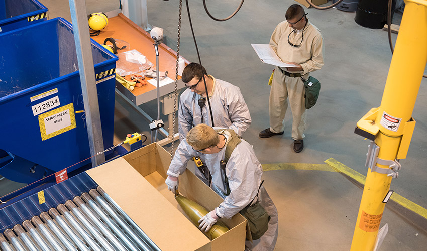 Munitions handlers lower a test projectile into a Static Detonation Chamber (SDC) loading box at the Blue Grass Chemical Agent-Destruction Pilot Plant. The SDC is in lockdown mode, where everything is being done as it will be during operations, scheduled to begin in late May.