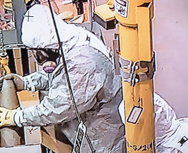 Munitions handlers place the first 155mm mustard-agent filled projectile slated for destruction into a feed box June 7. The projectile was automatically fed into the Static Detonation Chamber at the Blue Grass Chemical Agent-Destruction Pilot Plant and destroyed the same day. (Image taken from closed-circuit television.)
