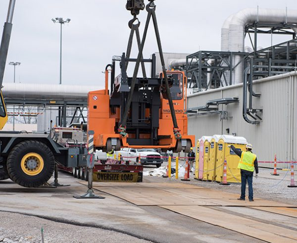 A worker directs crane operators as they unload a sideloader truck Jan. 18 that will be used to convey munitions transport containers inside the Blue Grass Chemical Agent-Destruction Pilot Plant during operations.