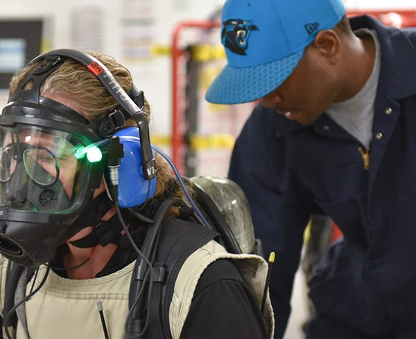 An operations support worker at the Pueblo Chemical Agent-Destruction Pilot Plant examines the air tank of a waste operator preparing for a Demilitarization Protective Ensemble entry in the Entry Support Area. The plant recently received high marks from U.S. Department of the Army Inspector General chemical surety inspectors.
