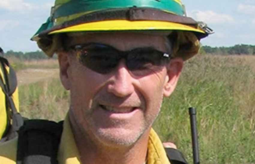 Tom Edwards, biologist assigned to the Blue Grass Army Depot, Kentucky Department of Fish and Wildlife Resources, smiles as he prepares for a prescribed burn of depot native grasslands. This planned and scheduled activity helps the grasslands flourish by burning back non-native species to allow the native ones more access to resources.